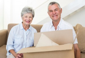 Cheerful senior couple moving into new home smiling at camera